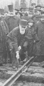 In this 1895 black and white photo, Donald Alexander Smith, surrounded by onlooking workers, bends low to swing the sledge hammer onto a railway spike set in the tie. This spike signalled the completion of a coast-to-coast rail system in Canada.
